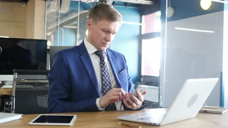 trabalhador de escritório : businessman surfing smartphone in office Stock Footage