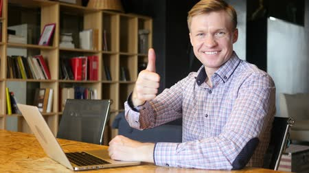 polegar : Happy smiling designer giving thumbs up to camera in creative office