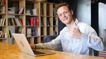 trabalhador de escritório : Serious handsome man in shirt sitting on workplace and shows thumbs up Stock Footage