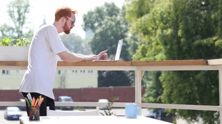 felicidade : Young Man Working on Laptop, Typing, Standing in Balcony Outdoor