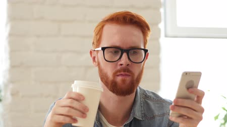 erkély : Man with Beard and Red Hairs Using Smartphone, Phone and Drinking Coffee, Tea
