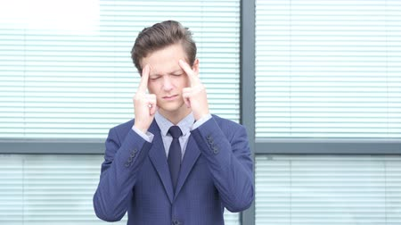 feszült : Headache Gesture by Young Businessman