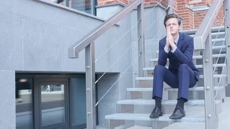 feszült : Tired Frustrated Young Businessman Sitting on Stairs Outside Office Stock mozgókép