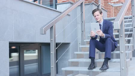 sala konferencyjna : Young Businessman Online Video Chat, Sitting on Stairs Outside Office