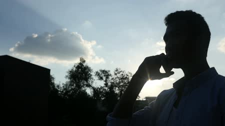 общаться : Black Man Talking on Phone, in front of Sun during Sunset, Silhouette Стоковые видеозаписи