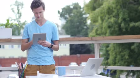 программное обеспечение : Sunny Day, Man Standing and Browsing on Tablet in Balcony, Gadget