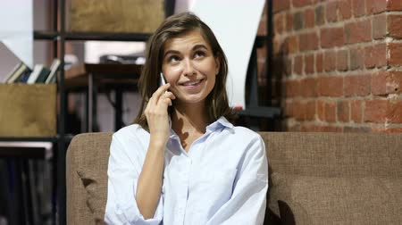 kulaklar : Happy Girl Attending Phone Call, Sitting in Loft Office Stok Video