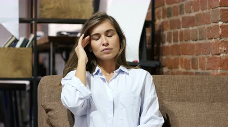 feszült : Headache, Girl Sitting on Sofa in Loft Office Stock mozgókép