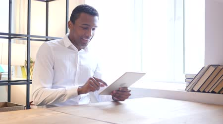 navegador : Black Man Using Tablet in Office