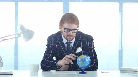 leitor : Redhead Businessman Reading World Globe with attention
