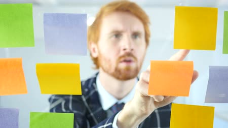projektant : Redhead Man Working On Sticky Notes Attached on Glass in Office Wideo