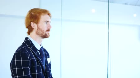 nápad : Side View of Pensive Redhead Businessman Looking through Office Window