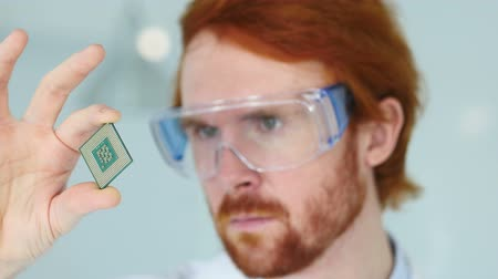 nanotechnologia : Man in Protective Glasses Looking for Computer Chip Wideo