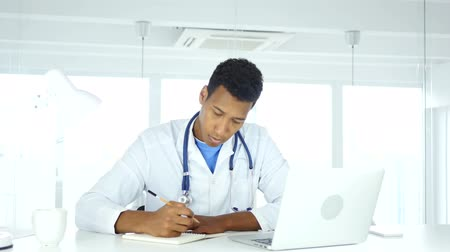 general practitioner : Afro-American Doctor Writing Medical Reports of Patient, Medicine
