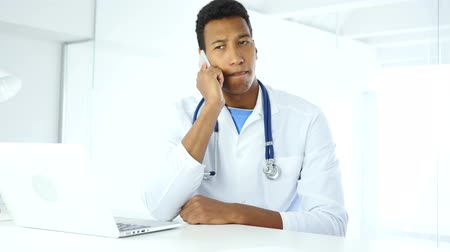 colega de trabalho : Afro-American Doctor Talking on Phone in Hospital Stock Footage