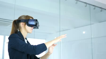 valóság : Woman Wearing virtual reality glasses in Office, using VR goggles headset