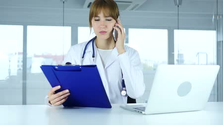 general practitioner : Young Female Doctor Holding Medical Reports, Talking on Phone