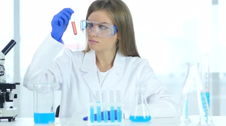 sallamak : Female Research Scientist Looking for a Red Solution in Test Tube in Laboratory