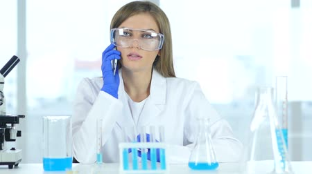 microbiologia : Female Scientist Talking on Phone in Laboratory