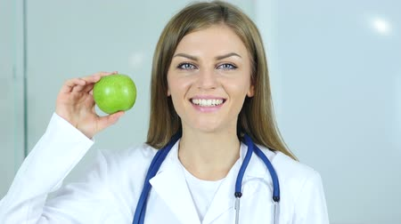 cita : Primer plano de la doctora Holding Green Apple en la mano Archivo de Video