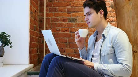 szomjúság : Portrait of Young Man Drinking Coffee and Working on Laptop