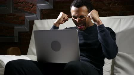 sikerül : Happy African Man Celebrating Success on Work on Laptop Stock mozgókép