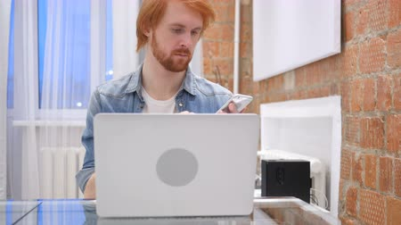 vöröshajú : Redhead Beard Man Browsing Online on Smartphone, Typing Stock mozgókép