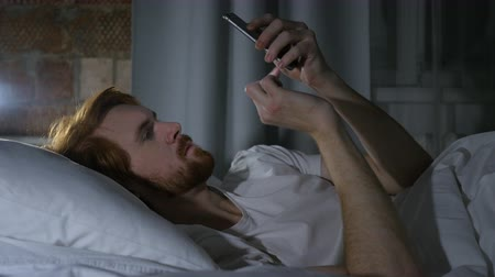 vöröshajú : Redhead Beard Man Browsing Email and Messages on Phone in Bed