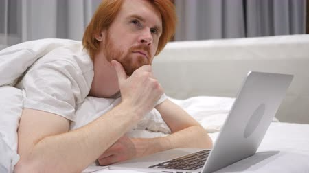 obličejový : Thinking Redhead Beard Man Working on Laptop Lying in Bed