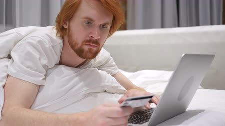 roodharige : Online winkelen door Redhead Beard Man in bed op laptop, betaling