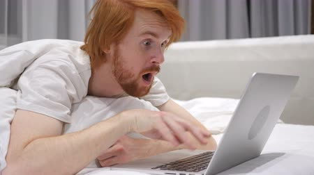 vöröshajú : Close Up of Shocked Redhead Beard Man working on Laptop in Bed