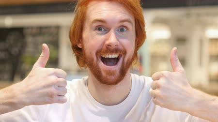 vöröshajú : Thumbs Up with Both Hands by Redhead Beard Man in Cafe
