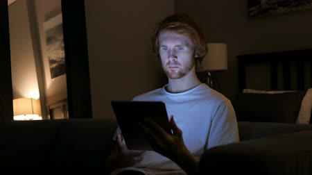 olhar : Redhead Man Using Tablet Computer at Night Stock Footage