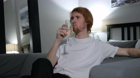 szampan : Relaxing Redhead Man Drinking Champagne Wine, Sitting on Couch