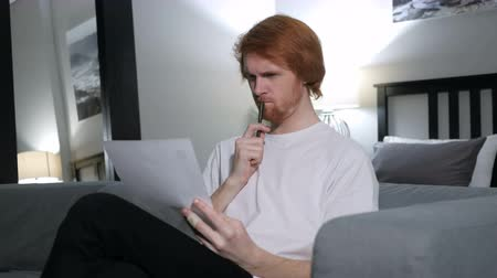 подпись : Penisve Redhead Man Reading Letter, Sitting on Sofa