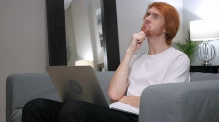 olhar : Pensive Redhead Man Working on Laptop in Bedroom Stock Footage