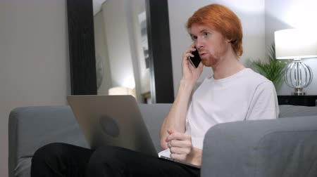 olhar : Redhead Man Talking on Phone while Working on Laptop Stock Footage
