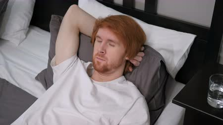 relaks : Young Tired Redhead Man Sleeping in Bedroom