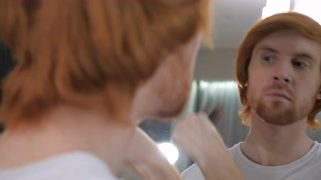 grzebień : Redhead Beard Man Combing Hairs in Mirror