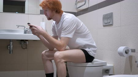 roodharige : Roodharige Man met Smartphone in Toilet, Commode