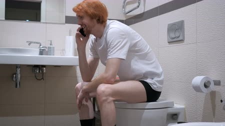 vöröshajú : Redhead Man Talking on Phone in Toilet, Commode Stock mozgókép