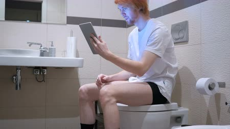 sala konferencyjna : Video Chat on Tablet by Man Sitting on the Bathroom Commode Wideo
