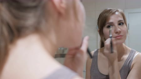 szminka : Young Woman Putting Make Up on Face in Mirror Wideo