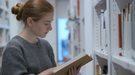 подпись : Redhead Woman Finding and Taking Books in Library