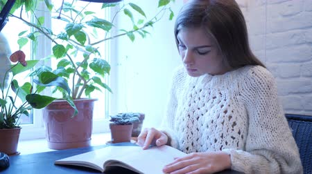 подпись : Young Woman Reading Book While Sitting in Office Стоковые видеозаписи