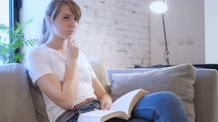 подпись : Penisve Woman Reading Book while Sitting on Sofa Стоковые видеозаписи