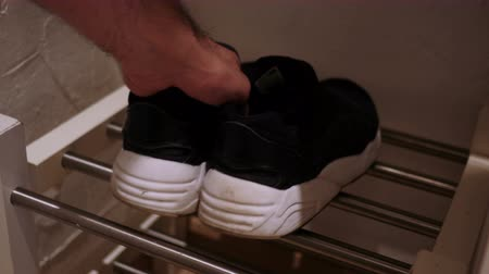 klapki : Close Up of Hands Putting Shoes on Shoe Reck