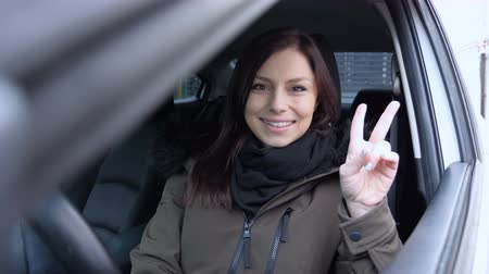 siker : Victory Sign by Young Woman Sitting in Car Stock mozgókép