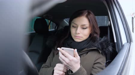 navegador : Woman Using Smartphone while Sitting in Car