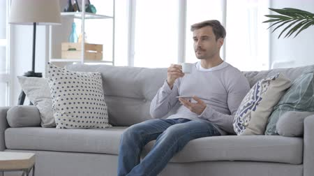 healthy office : Adult Man Drinking Coffee and Relaxing on Couch